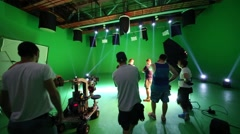 Film crew in green studio talking to each other on shooting video Stock Footage
