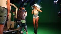 Bukatara correcting beads on her breast on shooting video Stock Footage
