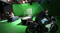 Actor on sport motobike moving in studio on shooting video Stock Footage