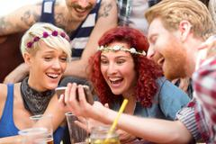 Curly ginger girl is delighted with photos on fellows mobile phone - stock photo
