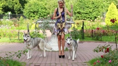 Blond woman with two Husky on dog-lead comes from flowerbed Stock Footage