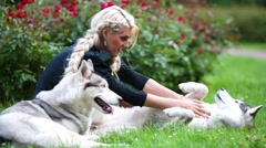Woman on lawn scratching bellies of two Husky dogs in park. Stock Footage