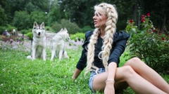 Blond woman and her two dogs Huskies behind on meadow in park. Stock Footage