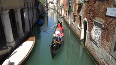 A gondola loaded with tourists cruises down a quiet backwater Venice canal Stock Footage