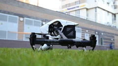 Black and white quadrocopter DJI Inspire standing on green grass Stock Footage