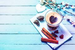 Cup of cappuccino with heart of cocoa on wooden table Stock Photos