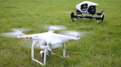 Black DJI Inspire and white DJI Phantom with turn on propellers Stock Footage