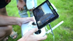 Houses in screen of tablet and quadrocopters remote control in hands Stock Footage