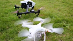 Two quadrocopters DJI Inspire and DJI Phantom standing on grass Stock Footage