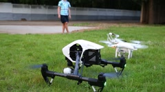 Quadrocopters  DJI Inspire and DJI Phantom on grass in front of fence Stock Footage