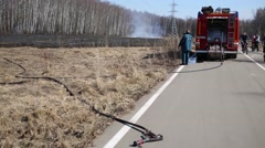 Fire hose, fire truck and firefighter digging burning remains of grass Stock Footage