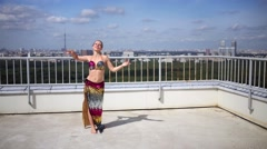 Woman dancing in Indian style on roof of tall building. Stock Footage