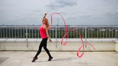 Blonde in red dancing gracefully with tape on roof of tall building. Stock Footage