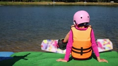 Little girl in life jacket and wakeboard siting in front of lake. Stock Footage