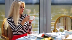 Blonde sitting at table in ship restaurant and drinking from cup. Stock Footage