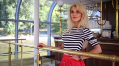 Woman in singlet standing at railing next to bar on ship restaurant Stock Footage