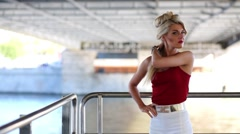 Luxury blonde standing at handrail of ship, sailing under bridge. Stock Footage