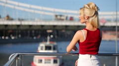 Blonde woman standing on stern of ship on background of bridge Stock Footage
