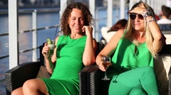 Two womans in green sitting in chair with glasses on deck of ship Stock Footage