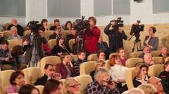 Spectators sitting in chairs, cameramen filmed in hall Stock Footage