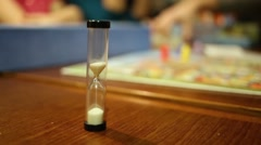 Hourglass, board game and people around table close up. Stock Footage