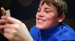 Boy in blue jacket with cards in hand smiling close up. Stock Footage