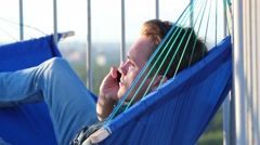 Young man lying in hammock blue and holding phone to his ear. Stock Footage