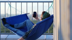 Man lying in hammock, holding smartphone and drives them around. Stock Footage
