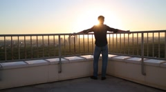 Guy is leaning on fence on roof and watching sunset. Stock Footage