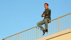 Young man sitting on fence on roof and puts his hands to sides. Stock Footage