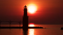 Time lapse red sunrise over vast lake with lighthouse, fishing boats Stock Footage