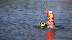 Girl in life-jacket and helmet holding rope and floating on water Stock Footage