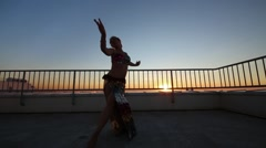 Beautiful woman dancing in Indian style in sunset on apartments roof. Stock Footage