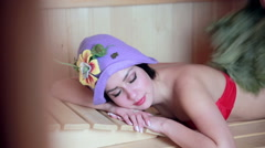 Young sexy girl sweating in the in wooden sauna. Lady hover brooms Stock Footage