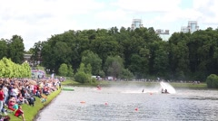 Sportsmans ATV and flyboard act in park on lake in front of audience Stock Footage