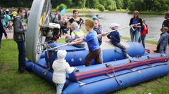 Little children playing on inflatable boat on celebration Fire and Rescue Stock Footage