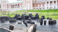 Miniature palace and park ensemble of metal, and behind real building Stock Footage