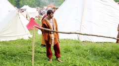 Two men in robes of ancient people make fence on historical festival Stock Footage