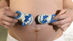 Pregnant woman holding blue booties Stock Footage