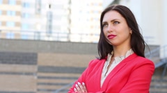 Brunette woman smiling and looking in red jacket in front of building Stock Footage