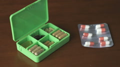 Woman's hand puts capsules pills in container Stock Footage