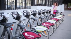 Woman chooses from row of bicycle rental on street parking Stock Footage
