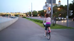 Woman riding bicycle along seafront to bridge next to Cathedral Stock Footage