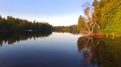 Gliding over mirror-smooth wilderness lake at daybreak - stock footage