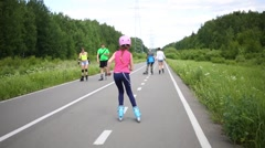 Girl blue helmet and pink roller riding snake on bike path in park. Stock Footage