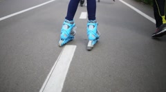 Blue rollers girl riding along bike path in park close up. Stock Footage
