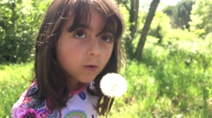 Baby girl blowing on Taraxacum, slow motion and defocused view Stock Footage