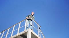 Man in denim trousers and shirt standing at railing on roof on sky. Stock Footage