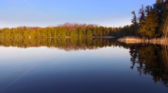 Gliding over mirror smooth wilderness lake at daybreak - stock footage