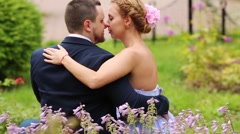 Couple sitting on grass back among flowers ang turning. Stock Footage